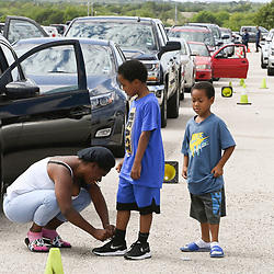 Austin, TX USA August 26, 2020: Valencia Trower of Beaumont helps her children as Austin officials help east Texans and west Louisiana residents get settled at the Circuit of the Americas race track after evacuating low-lying areas about to get hit by Hurricane Laura on the Gulf Coast. Laura is expected to make landfall overnight as a Category 4 storm and wreak havoc along the Texas coast and inland.