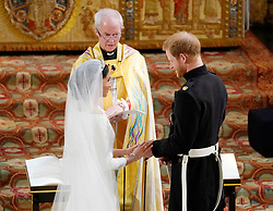 File photo dated 19/05/18 of the Duke and Duchess of Sussex in St George's Chapel at Windsor Castle during their wedding service, conducted by the Archbishop of Canterbury Justin Welby, as they are preparing for the christening of their son Archie, which will take place on Saturday.