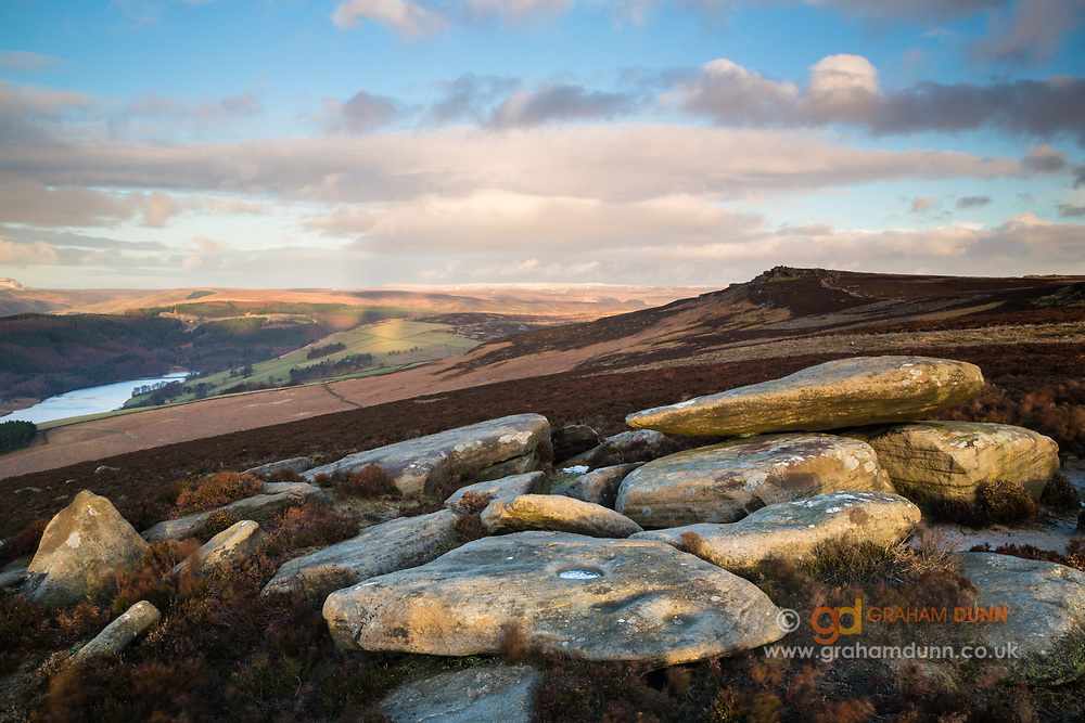 Dappled morning light highlights the foreground boulders on Derwent Edge. White Tor, Ladybower Reservoir and a snow-covered Bleaklow can be seen in the distance. Winter, February in Derbyshire, Peak District National Park, England, UK. Landscape