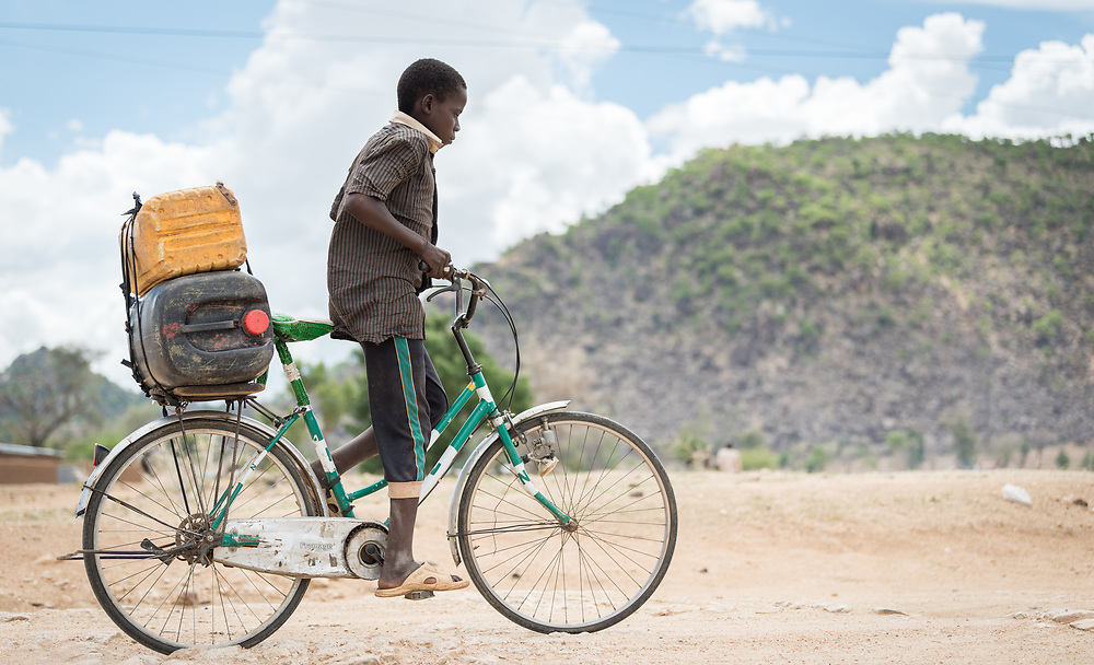 30 May 2019, Mokolo, Cameroon: A young boy rides his bike towards the market in Minawao. The Minawao camp for Nigerian refugees, located in the Far North region of Cameroon, hosts some 58,000 refugees from North East Nigeria. The refugees are supported by the Lutheran World Federation, together with a range of partners.