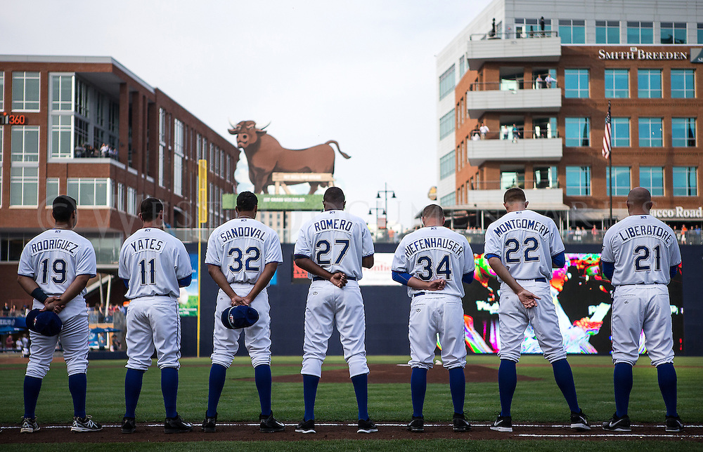 The Durham Bulls take a moment of silence before the start of the game on Opening Day at the Durham Bulls Athletic Park on April 3. A crowd of 9,483 turned out to watch the 2013 Governors' Cup champions in their season opener against the Gwinnett Braves. Late in the game Jerry Sands (35) hit a game-tying home run to help the Bulls rally past the Braves 7-6.