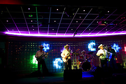 """A group of Norteno musicians play music at a night club in downtown Culiacan.  Norteno music is famous for its """"corridos"""", or ballads.  Many musicians compose corridos about drug lords that become part of popular culture."""