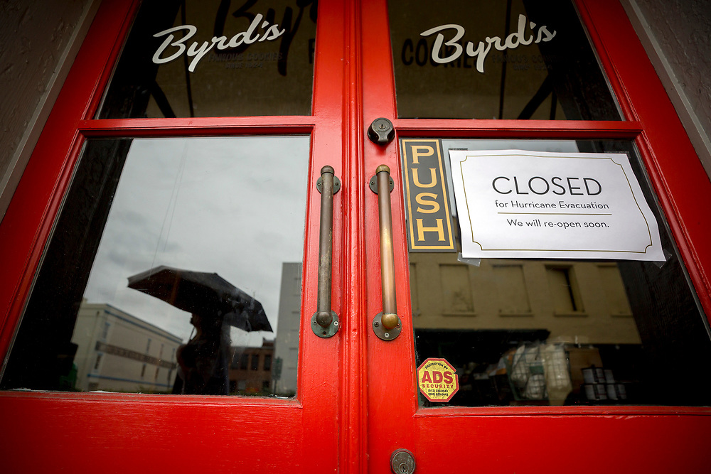 A woman with and umbrella walks past the closed Byrd's Cookie store, Sunday, Sept., 10, 2017 in downtown Savannah, Ga. Winds from the outside bands of Hurricane Irma are expected to impact Savannah later today. (AP Photo/Stephen B. Morton)