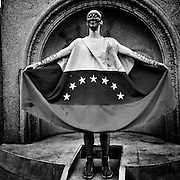 Caracas - Venezuela. An artist performs an act dressed with a Venezuelan flag to call for tolerance and dialogue between the opposing positions in Venezuela. In Altamira Square, main bastion of opposition, many performances and peaceful manifestations have been taking place today for second day in a row after the end of violent clashes between opposers to the government and militar forces.