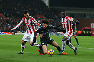 Leroy Sane of Manchester City © is stopped by Maxim Choupo-Moting (l) and Badou Ndiaye of Stoke City. Premier league match, Stoke City v Manchester City at the Bet365 Stadium in Stoke on Trent, Staffs on Monday 12th March 2018.<br /> pic by Andrew Orchard, Andrew Orchard sports photography.