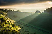 First light breaks over Peter's Stone and illuminates the banks of Cressbrook Dale, Derbyshire. A beautiful Spring morning in the Peak District National Park, England, UK.