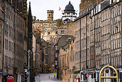 Edinburgh, Scotland, UK. 18 April 2020. Views of empty streets and members of the public outside on another Saturday during the coronavirus lockdown in Edinburgh. Female runner on the Royal Mile. Iain Masterton/Alamy Live News