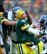 Green Bay's Brett Favre is hit by Seattle's Marcus Tubbs after throwing a 10-yard pass to Donald Lee in the 4th quarter. Favre seemed to injure his left shoulder on the play. .The Green Bay Packers hosted the Seattle Seahawks at Lambeau Field Sunday January, 1, 2006. Steve Apps-State Journal.