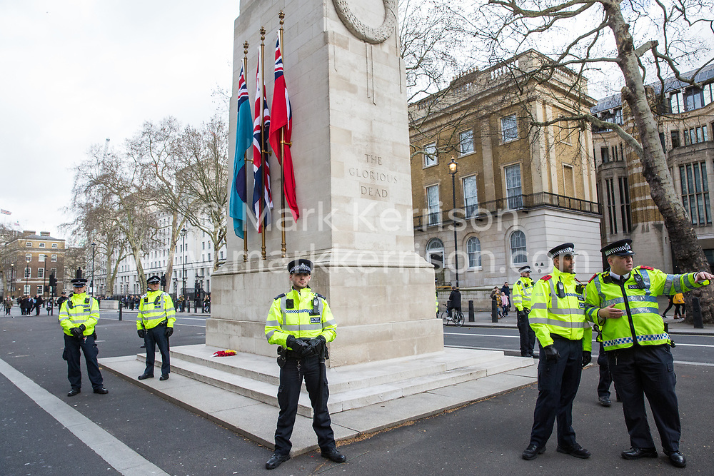 London, UK. 9th March, 2019. Metropolitan Police officers stand around the Cenotaph as climate activists from Extinction Rebellion prepare to pour artificial blood on the ground outside Downing Street as part of an act of civil disobedience named 'The Blood of Our Children' to call on the Government to take immediate steps to combat the current climate and ecological emergency.