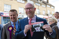 """© Licensed to London News Pictures. 20/05/2017. LONDON, UK.  PAUL NUTTALL, UKIP leader holds a leaflet showing a picture of Theresa May, captioned """"Beware of scams"""" as he campaigns in Elm Park with UKIP candidate for Dagenham and Rainham, PETER HARRIS. All political parties continue to campaign across the UK ahead of the general election taking place on 8th June. Photo credit: Vickie Flores/LNP"""