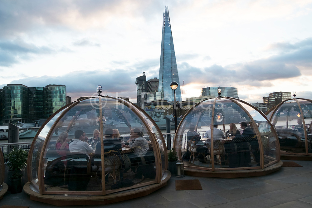 Pop up igloos being used for diners outside a hotel restaurant opposite The Shard in London, England, United Kingdom.