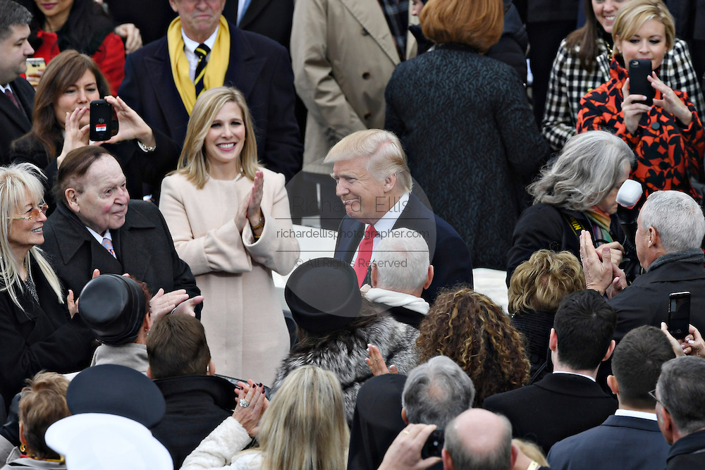 President elect Donald Trump smiles as he arrives to applause for his inauguration as the 45th President on Capitol Hill January 20, 2017 in Washington, DC. American casino magnate Sheldon Adelson stands to the left