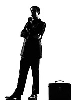 one silhouette caucasian business man thinking pensive attitude behavior with briefcase full length on studio isolated white background