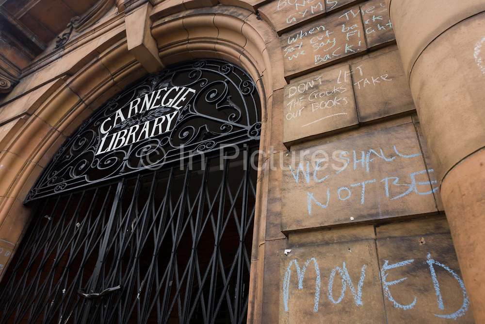 Campaigners locked out of the closed Carnegie Library have written messages in chalk on the front entrance in Herne Hill, south London on 7th May 2016. For ten days, members of the community in the south London borough occupied their important resource for learning and social hub for the weekend. But after a long campaign by locals, Lambeth have gone ahead and closed the librarys doors because they say, cuts to their budget mean millions must be saved. A gym is planned to replace the working library and while some of the 20,000 books on shelves will remain, no librarians will be present to administer it. London borough's budget cuts mean four of its 10 libraries will either close, move or be run by volunteers.