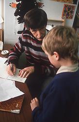 Junior school teacher and pupil in classroom,
