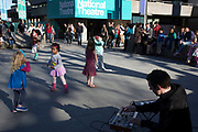 Children spontaneously start to dance to music being made by a busker, as she starts to draw in a crowd who watch her. The South Bank is a significant arts and entertainment district, and home to an endless list of activities for Londoners, visitors and tourists alike.