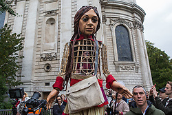 London, UK. 23rd October, 2021. Little Amal, a giant puppet of a Syrian refugee girl fleeing conflict, walks from St Paul's Cathedral to the Globe Theatre. The 3.5-metre puppet, which is nearing the end of an 8,000km journey from the Turkish-Syrian border to Manchester in support of refugees, climbed the steps of St Paul's Cathedral to present a wood carving of a ship at sea from St Paul's birthplace at Tarsus in Turkey to the dean. Credit: Mark Kerrison/Alamy Live News