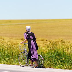 Gordonville, PA, USA / June 8, 2020: A young Amish girl uses her bare feet to push a bicycle scooter along a rural  road in Lancaster County.