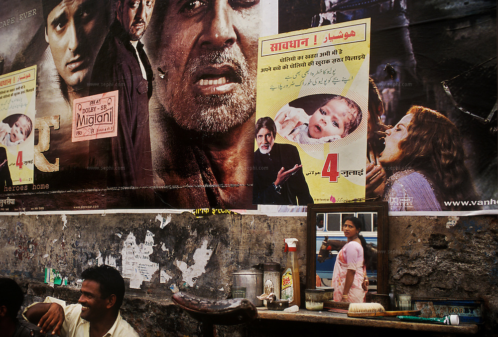 Street scene in Moradabad (Uttar Pradesh). A woman passing by a wall with posters of latest movies and a promotion poster for the polio campaign, both featuring Amitabh Bachchan, India's most famous movie star who endorses the campaign.