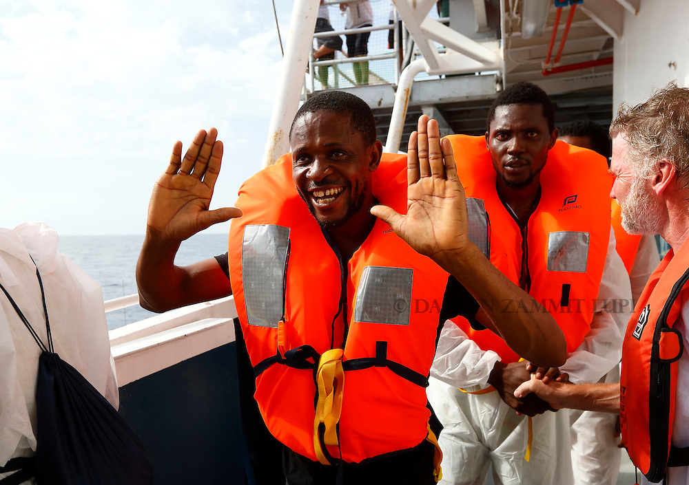 A migrant thanks the crew of the Migrant Offshore Aid Station (MOAS) ship MV Phoenix before being transferred to an Italian Coast Guard vessel after being rescued some 20 miles (32 kilometres) off the coast of Libya, August 3, 2015.  118 migrants were rescued by MOAS from a rubber dinghy off Libya on Monday morning . The Phoenix, manned by personnel from international non-governmental organisations Medecins san Frontiere (MSF) and MOAS, is the first privately funded vessel to operate in the Mediterranean.<br /> REUTERS/Darrin Zammit Lupi <br /> MALTA OUT. NO COMMERCIAL OR EDITORIAL SALES IN MALTA