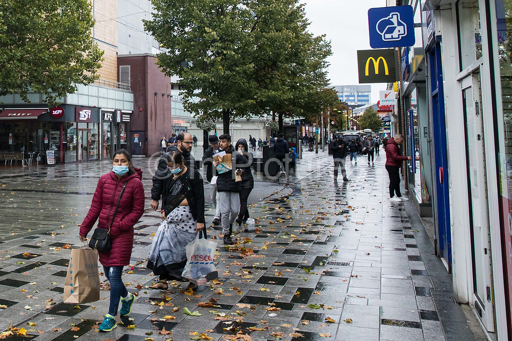 Members of the public wearing face coverings to help prevent the spread of the coronavirus carry shopping bags on 4 October 2020 in Slough, United Kingdom. Slough Borough Council confirmed on 2nd October that its coronavirus infection rate is the highest in the south of England and Slough MP Tan Dhesi asked Health Secretary Matt Hancock in Parliament whether the local test centre in Montem Lane could be reverted to permit walk-in and drive-in visits without an appointment.