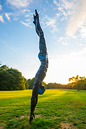 """Old Westbury, New York, U.S., September 1, 2019. """"Athlete III - Deep Plunge"""" is one of 33 outdoor sculptures by Jerzy Kedziora (Jotka), b. 1947 in Poland,, and his Balance in Nature art is on view at historic Old Westbury Gardens in Long Island, until October 20, 2019. Seen at dusk, the life-size, bronze resin balancing sculpture, dressed in blue swimwear, appears about to dive into the lawn."""