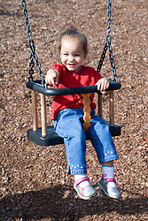 Young girl swinging on a playground swing,