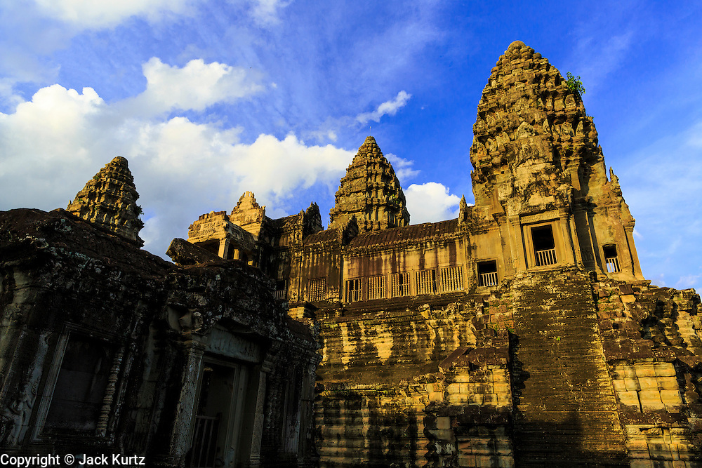 """01 JULY 2013 - ANGKOR WAT, SIEM REAP, SIEM REAP, CAMBODIA:  The center courtyard of Angkor Wat late in the afternoon. Angkor Wat is the largest temple complex in the world. The temple was built by the Khmer King Suryavarman II in the early 12th century in Yasodharapura (present-day Angkor), the capital of the Khmer Empire, as his state temple and eventual mausoleum. Angkor Wat was dedicated to Vishnu. It is the best-preserved temple at the site, and has remained a religious centre since its foundation– first Hindu, then Buddhist. The temple is at the top of the high classical style of Khmer architecture. It is a symbol of Cambodia, appearing on the national flag, and it is the country's prime attraction for visitors. The temple is admired for the architecture, the extensive bas-reliefs, and for the numerous devatas adorning its walls. The modern name, Angkor Wat, means """"Temple City"""" or """"City of Temples"""" in Khmer; Angkor, meaning """"city"""" or """"capital city"""", is a vernacular form of the word nokor, which comes from the Sanskrit word nagara. Wat is the Khmer word for """"temple grounds"""", derived from the Pali word """"vatta."""" Prior to this time the temple was known as Preah Pisnulok, after the posthumous title of its founder. It is also the name of complex of temples, which includes Bayon and Preah Khan, in the vicinity. It is by far the most visited tourist attraction in Cambodia. More than half of all tourists to Cambodia visit Angkor.      PHOTO BY JACK KURTZ"""
