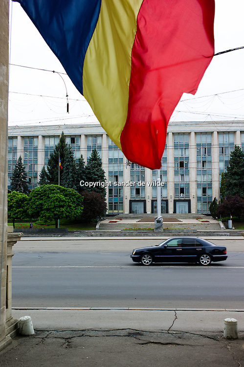 An typical soviet style building  in Chisinau, Moldova with new Mercedes car passing by in the city center traffic axe, shot from under the arch of triomph where the national flag hangs