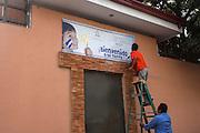 """Trabajadores colocan un nuevo letrero afuera del albergue de menores migrantes deportados """"Belén"""" en San Pedro Sula. (Prometeo Lucero)"""