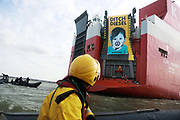 A giant banner at the back of the cargo ship Elbe Highway calling for VW to ditch diesel September 21st 2017, Thames Estuary, Kent, United Kingdom. Greenpeace volunteers in kayaks, speed boats and climbers on the jetty prevent the 23,498-tonne cargo ship Elbe Highway from docking at Sheerness in Kent.  The cargo ship is bringing Volkswagen diesel cars into the UK and the Greenpeace action is to prevent this from happening and to make VW ditch diesel. Two climbers board the ship and hang a banner on the roll-on roll-off part of the ship preventing any cars from being off-loaded. The action is part of a long running Greenpeace campaign to curb diesel emmissions and air pollution broght on by diesel cars.