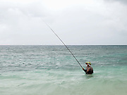 A Sasak fisherman fishing with a rod and line off Senggigi beach, Lombok, Indonesia. The predominantly Muslim Sasak people are the native inhabitants of Lombok where they form 85% of the population.