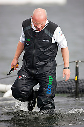 Kiel - Germany, 28th of August 2009. iShares cup. First day of racing...The first racing day consisting of 8 races. Picture shows Ecover just after they capsized between race 3 and 4.  Mike Golding walks on the netting of the upturned hull with a knife in his hand.