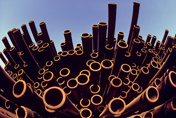 Stack of multiple pipes with clear blue sky background.