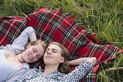 Young couple resting on blanket in a meadow, Bavaria, Germany