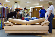 Moscow, Russia, 18/06/2006..A member of staff demonstrating sofabeds to customers in a branch of the Shatura furniture store chain.