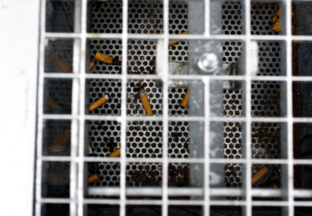 Nederland Rotterdam 23 november 2008 20081123 .De eerste asbaktegel van Nederland. De gemeente Rotterdam start als eerste gemeente van Nederland een proef met de asbaktegel. Gedurende drie maanden wordt op zes locaties in het centrum van de stad de asbaktegel getest. Sinds het rookverbod in openbare ruimtes, werkruimtes en de horeca roken er veel meer mensen op straat. Het gevolg hiervan is dat meer sigarettenpeuken op de stoep belanden. Een doorn in het oog van velen inwoners en bezoekers van de stad. De sigarettenpeuken ontsieren het straatbeeld en zijn slecht voor het milieu. Om de leefomgeving te ontlasten van de sigarettenpeuken is een  oplossing bedacht: de asbaktegel. De tegel is een asbak voor in de buitenruimte die in de stoep is verzonken. De bovenkant is een rooster waar sigarettenpeuken en kauwgom in gedeponeerd kunnen worden. Rotterdam is the first city to start a trial with an ashtray tile. Since the prohibition of smoking in public areas, more people are smoking on the streets. That results in more cigarettes on the streets. ..Foto: David Rozing