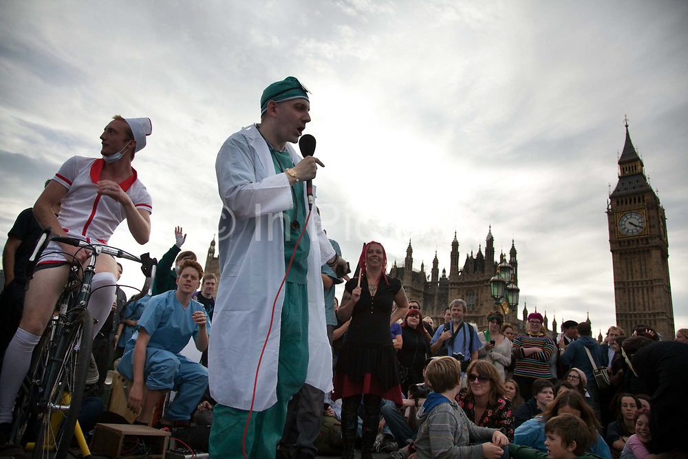Compere Chris Coltrane presenting the next show on Westminster Bridge.<br /> The Health and Care Bill has been passed by Parliament and is due to go to the House of Lords. In protest against the bill which aim to deconstruct and privatise large parts of the NHS UK Uncut activists together with health workers and trade unionists blocked the Westminster Bridge from 1pm til 5.30pm.