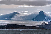 "Two of the peaks composing ""Tre Kroner"" covered in morning clouds at the bottom of Kongsfjorden (Kings Bay), Svalbard, Norway.  Part of Kronbreen (Crown Glacier) lies in the foreground."