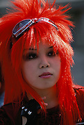 A teenage girl with bright orange hair at Harajuku.  Tokyo, Japan.