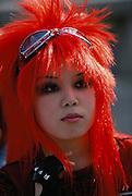 A teenage girl with bright orange hair at Harajuku.  Tokyo, Japan.