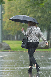 © Licensed to London News Pictures.28/09/2021. Builth Wells, Powys, Wales, UK. People walk through heavy rainfall in Builth Wells in Powys, Wales, UK. Photo credit: Graham M. Lawrence/LNP