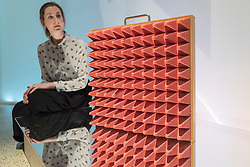 "© Licensed to London News Pictures. 06/11/2018. LONDON, UK. A staff member views ""Electro-Draught Excluder, Placebo Series"", 2001, by Dunne & Raby. Preview of ""Home Futures"", at the Design Museum.  The exhibition, in partnership with IKEA Museum Almhult, asks are we living in the way that pioneering architects and designers once predicted, or has our idea of home proved resistant to real change?  More than 150 objects and experiences are on display 7 November to 24 March 2019.  Photo credit: Stephen Chung/LNP"