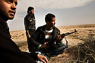 Youths watch a battle between Qadaffi forces in rebels in Braga on March 2, 2011.