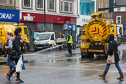 Workers clean up displaced gravel and mud as they prepare to dig up a large burst water main just yards from the entrance to Tooting Broadway station in South London. London water supply companies are battling a series of burst mains following the recent cold weather brought on by 'The Beast From The East'. London, March 07 2018.