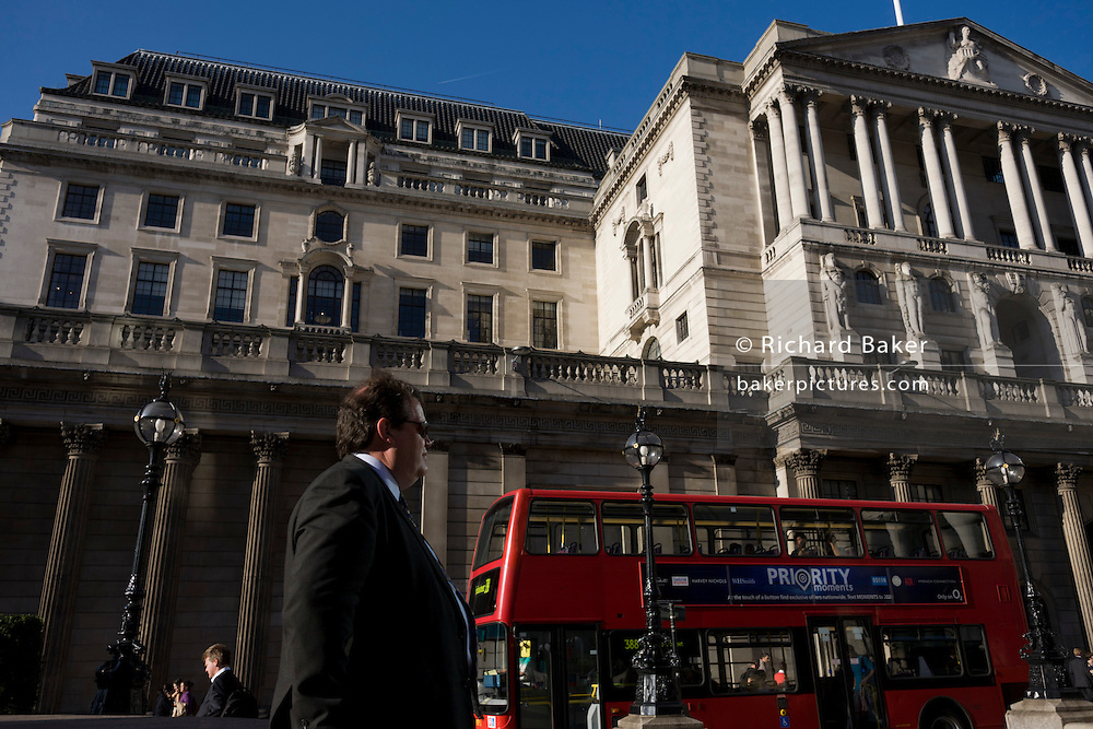 A businessman and red London bus beneath the Bank of England in Bank triangle in the City of London.