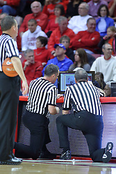 22 December 2013:  referees Mark Whitehead, Brent Hampton,  and Mike Stuart gather around the replay screen during an NCAA  mens basketball game between the Blue Demons of DePaul falling to  the Illinois State Redbirds 69-64 in Redbird Arena, Normal IL