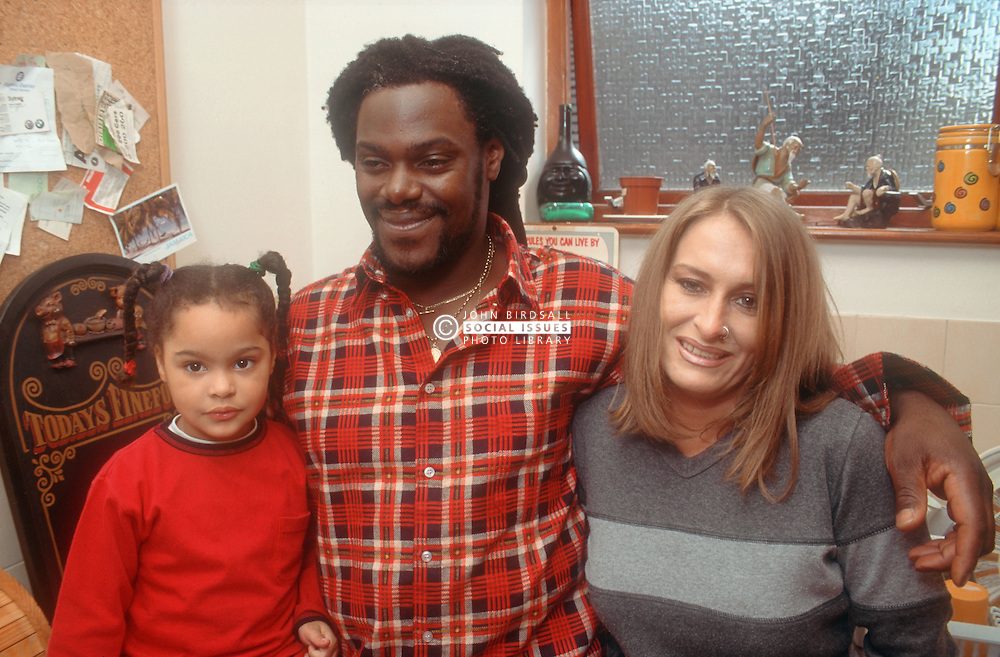 Multiracial family standing together in kitchen smiling,