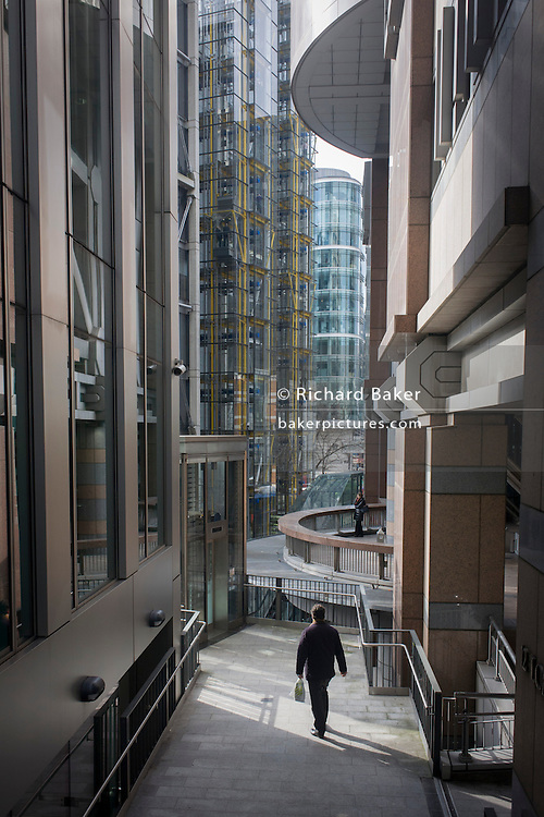 Surrounded by the tall, glass windows of company offices, a single person walks along a highwalk on London Wall (the line of the original Roman city limit) in the capital's financial district, known as the City of London - or Square Mile. Tall glass-covered buildings are everywhere as the lone man makes his way towards a nearby office complex. The City of London is the capital's historic centre first occupied by the Romans then expanded during following centuries until today, it has a resident population of under 10,000 but a daily working population of 311,000.