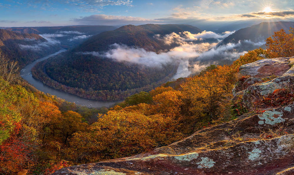 A thin layer of fog rolls through the New River Gorge of West Virginia on an autumn morning at Grandview State Park.
